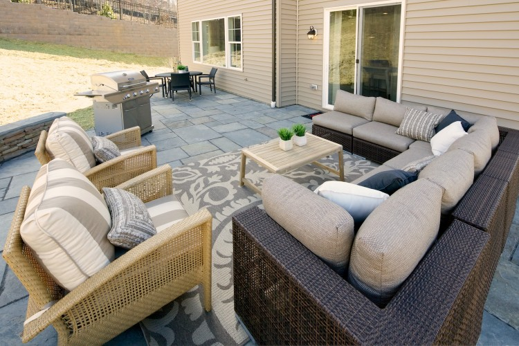 Slate patio with sofa, chairs, table, and grill