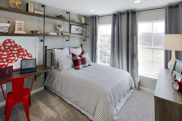 Bedroom with striped comforter on bed in front of window