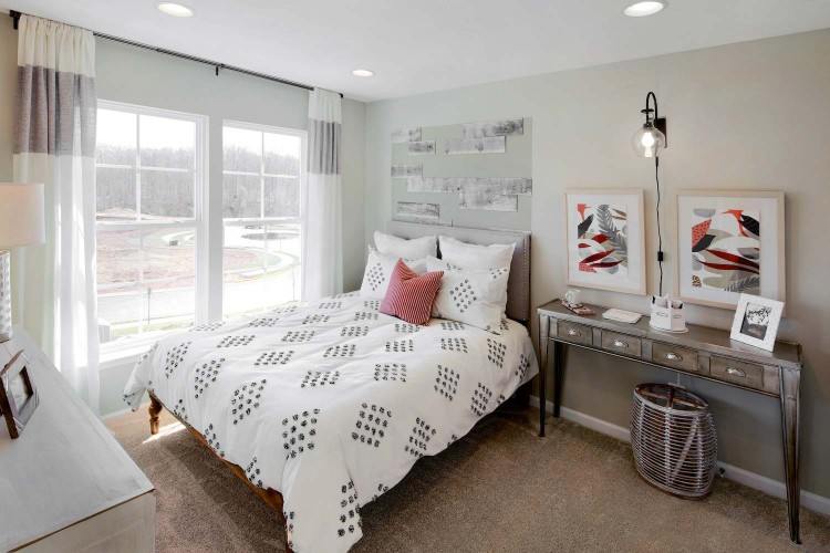Bedroom with spotted comforter on bed in front of window