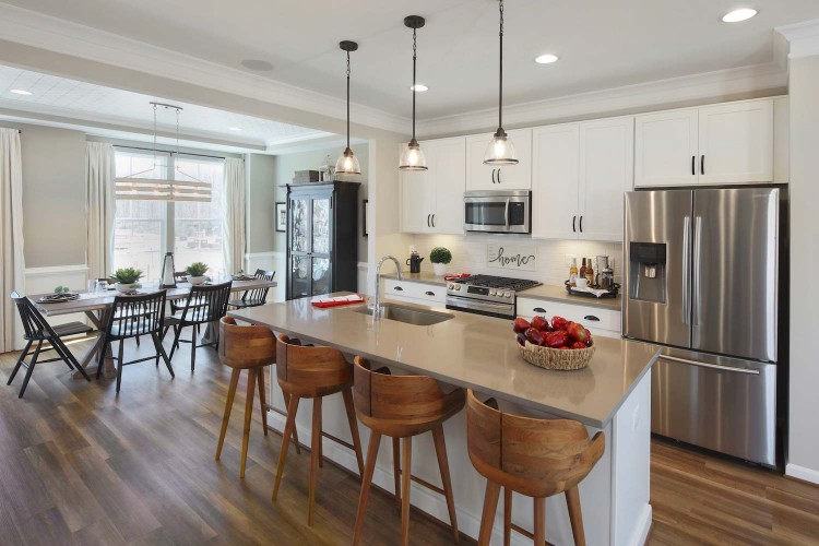 Great room showing eat in kitchen with wood stools and dining room